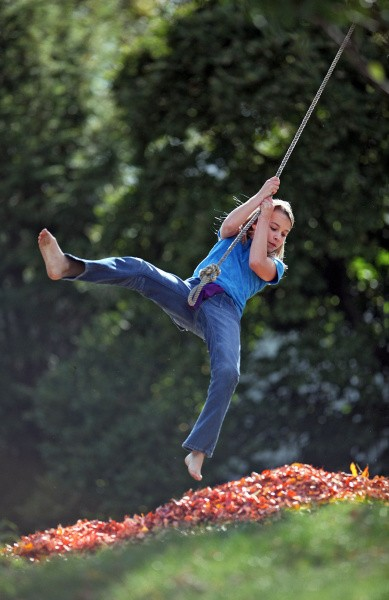 <b>Soft landing</b> | Madison Newman, 11, uses a rope swing to sail into a pile of leaves in her yard in Bexley. She was playing with her 6-year-old brother, Marshall, after school this week.